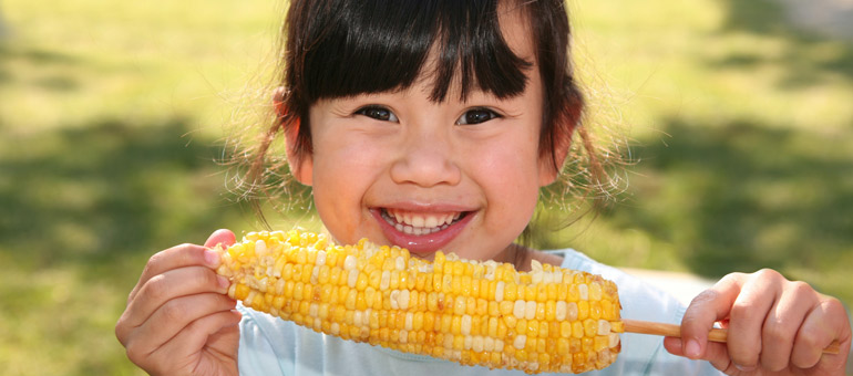 Young girl smiling while eating corn