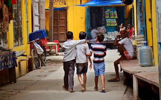 Children walking in the streets of India hugging each other